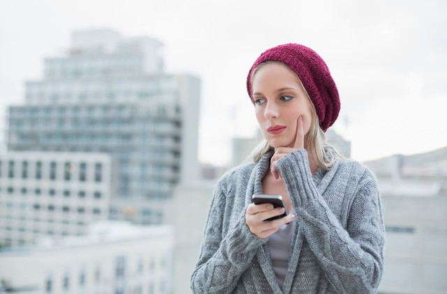 Thoughtful pretty blonde text messaging outdoors on urban background