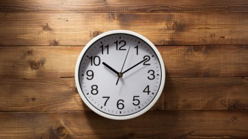 wall clock at wooden background