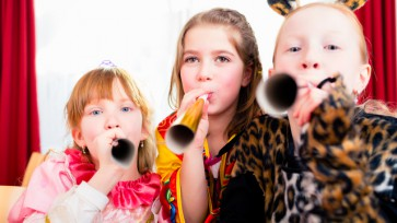 Kids with noisemakers making noise on party