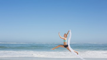 Fit woman jumping gracefully on the beach with scarf on a sunny day