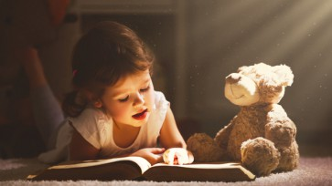 Little child girl is reading a book in evening in dark with a to