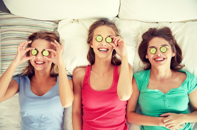 happy young women with cucumber mask lying in bed