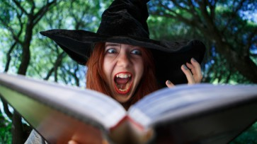 Portrait of witch with open magic book