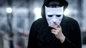 Mystery hoodie man holding white mask