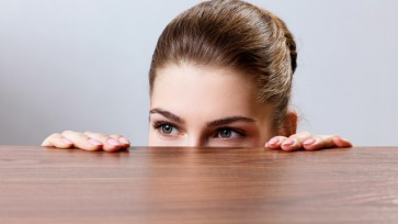 Woman peeping under the edge of wooden table
