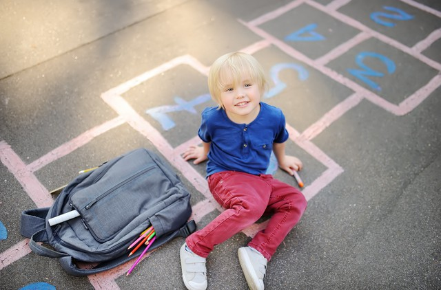 Cute blond boy doing homework sitting on school yard after school with bags laying near