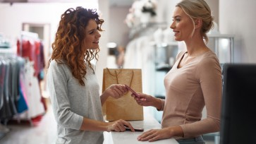 Young smiling lady giving credit card on register