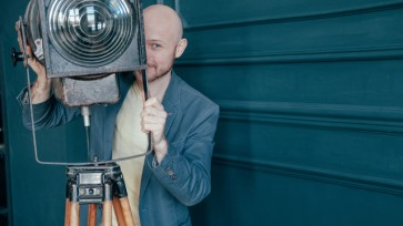 Attractive adult bald man with beard in suit looking around old lighting fixture, video light