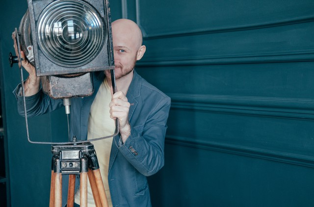 Attractive adult bald man with beard in suit looking around old lighting fixture, video light