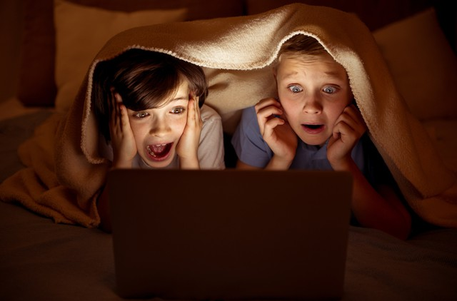 Fearful schoolboys watching scary movie