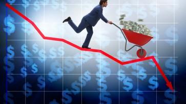 Businessman pushing money wheelbarrow down the chart