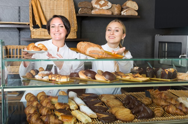Smiling woman and young girl reccomending pastry