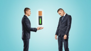 Two businessmen, one posing as if manually controlling the battery suspended in the air, the other standing half-turned with a sad expression on his face.