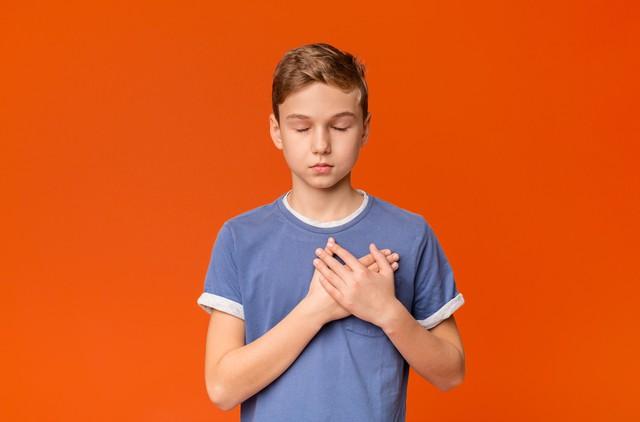 Sensitive teenage boy pressing hands to chest being grateful