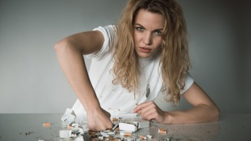 Willful young woman against smoking